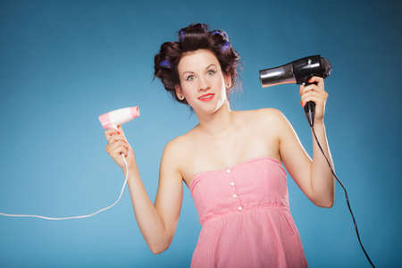 blow drier: Young woman preparing to party having fun, funny wide eyed girl styling hair with two hairdreyers retro style on blue