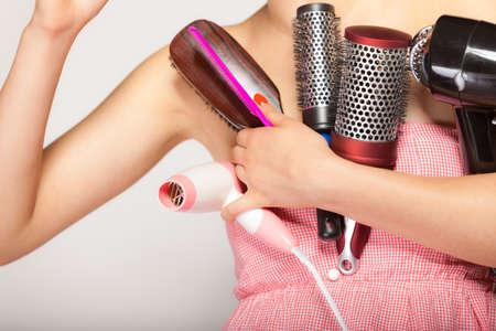 secador de pelo: mujer preparando para la fecha, el peinado del cabello chica con muchos accesorios peine hairdreyer cepillo en gris