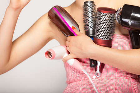 hair style: woman preparing for date, girl styling hair with many accessories comb brush hairdreyer on  gray