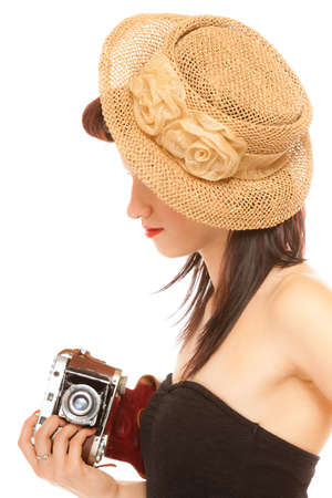 Beautiful photographer. Cute lovely retro style summer teen girl in hat holding using vintage old camera isolated on white background photo