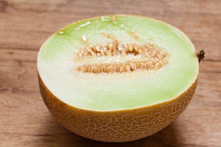 pips: Closeup of melon with pips on wooden table. Fruit, diet and healthy nutrition.