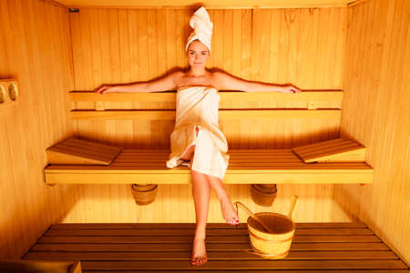 sauna: Spa beauty well being and relax concept. Woman in full length white towel sitting relaxed in wooden sauna
