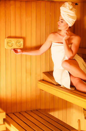 hygrometer: Beauty health spa concept. Woman relaxing in sauna interior looking on equipment thermometer and hygrometer. Stock Photo