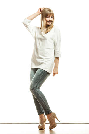 Fashion. Young blonde woman denim pants white bat sleeve top high heels. Female model posing in full length isolated photo