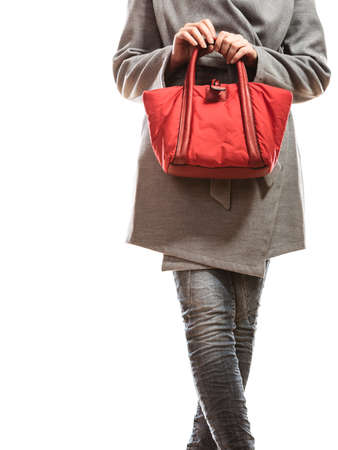 Fashion beauty and elegance concept. Closeup fashionably woman elegant gray belt coat holding red handbag isolated on white photo