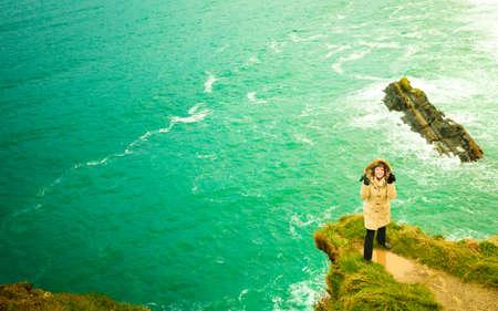irish landscape: Irish atlantic coast. Woman tourist standing on rock cliff by the ocean Co. Cork Ireland Europe. Beautiful sea landscape beauty in nature.