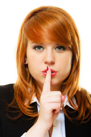Business woman redhaired girl asking for silence or secrecy with finger on lips hush hand gesture. Isolated photo