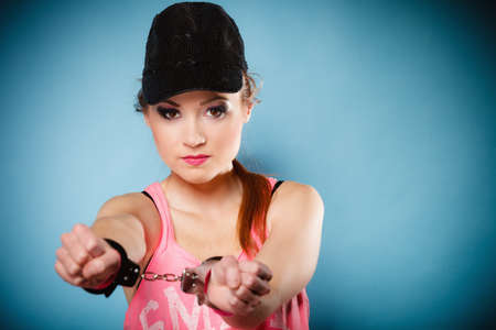 manacles: Teen crime, arrest and jail - Criminal teenager girl prisoner woman in handcuffs blue background