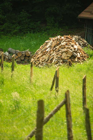 wood heating: pile of wood behind wooden, rusty metal damaged old fence on a green grass. heating, lumberjack, woodman