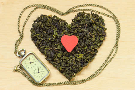 preventing: Diet healthcare tea time concept. Green tea heart shaped on wooden surface. Healthy food drink for lower heart disease risk Stock Photo