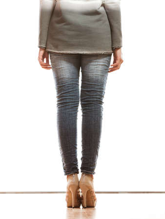 butt tight jeans: Fashion. Woman legs in denim trousers platform high heels shoes casual style back view isolated