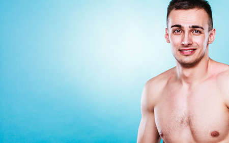 nacked: Sporty and healthy muscular man portrait blue background