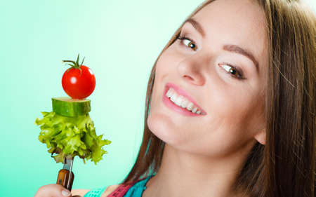 Dieting, healthcare and weight loss concept. Sporty girl fitness woman with measuring tape on neck and holding fork with fresh mixed vegetables on green blue background. Studio shot. photo