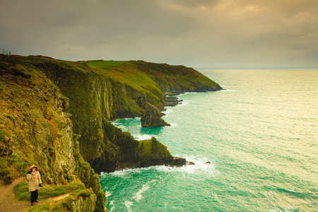 irish woman: Irish atlantic coast. Woman tourist standing on rock cliff by the ocean Co. Cork Ireland Europe. Beautiful sea landscape beauty in nature.