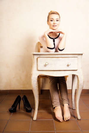 bare foot girl: Vintage style. Full length of barefoot girl student or businesswoman sitting on the wooden chair at the white retro desk. Design. Stock Photo
