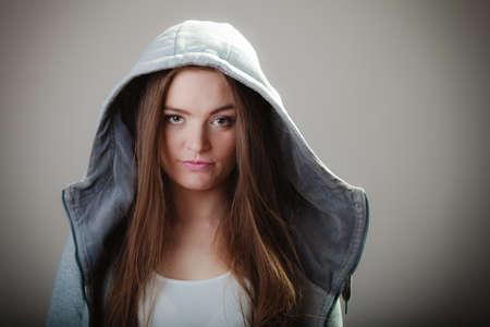sweatshirt: Retrato de pelo largo joven muchacha adolescente mujer en la sudadera con capucha sobre fondo gris