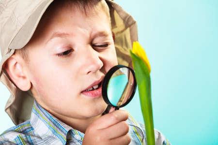 environmental education: Desarrollo de los ni�os. Ni�o flor de examen busca a trav�s de una lupa. La educaci�n sobre el medio ambiente. Foto de archivo