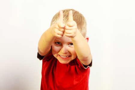 carita feliz: Infancia feliz. Retrato de la sonrisa divertida muchacho rubio ni�o en edad preescolar ni�o que muestra el pulgar en se�al de �xito gesto de la mano. Indoor. Foto de archivo