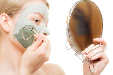 mud girl: Skin care. Woman in clay mud mask on face with heart on cheek looking in the mirror isolated on white. Girl taking care of dry complexion. Beauty treatment.