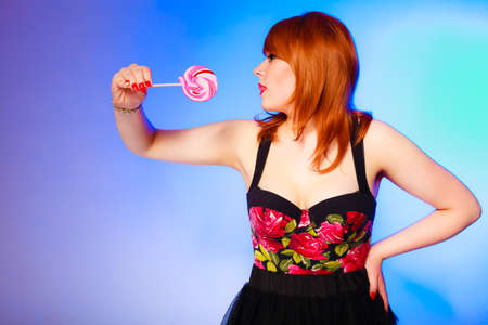 under control: Candies under control. Snack concept. Pretty red haired girl with lollipop in hands on blue background. Studio shot.