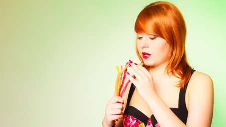 red haired woman: Dependence on sweets. Young red haired woman with candy on green background in studio.