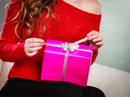 People celebrating xmas love and happiness concept - beauty girl opening present pink gift box sitting on sofa at home photo