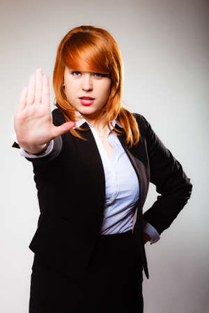 interdiction: Redhair businesswoman with stop hand sign gesture on gray. Business concept. Studio shot. Stock Photo