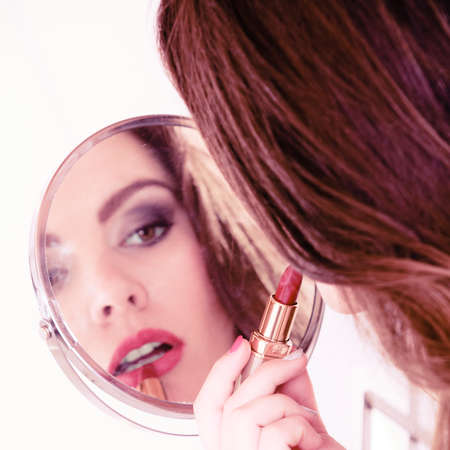 Applying make up concept. Beautiful woman with red lipstick in front of mirror. Indoor. photo
