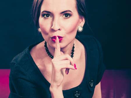 ? ?  ? �silence: Moda belleza y elegancia concepto. Mujer dedo estilo retro en los labios rojos. Se�ora elegante que muestra signo de silencio la mano, diciendo hush estar tranquilo en negro Foto de archivo