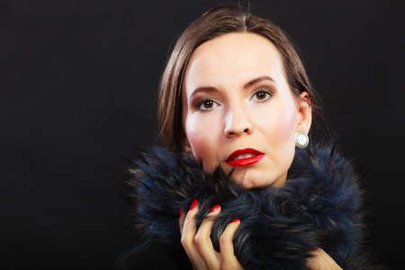 Fashion and beauty.  Woman in fur coat red lips and nails, lady retro style portrait on black background photo