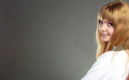 Face of young blonde woman with bangs gray background copy space text area