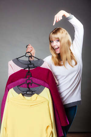 Retail and sale. Blonde girl fashionable woman showing clothes. Client customer pointing with finger hangers with colorful clothing gray background photo