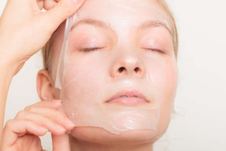 Belleza cosméticos cuidado de la piel y el concepto de salud. Primer rostro de mujer joven, muchacha que quita facial mascarilla exfoliante en gris. Descamación Foto de archivo