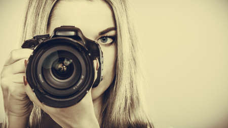 Photographer girl shooting images. Attractive blonde woman taking photos with camera. Filtered photo