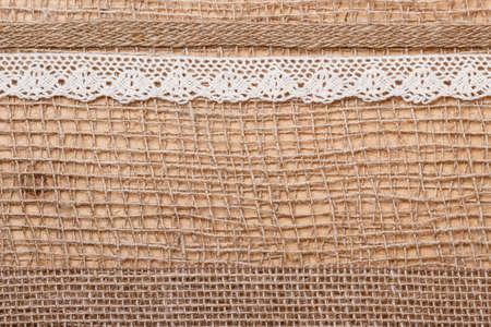 bagging: Lace and jute bagging ribbon on brown mesh material, natural burlap background