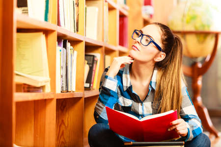 college: Education school concept. Clever female student hair ponytail girl blue glasses sitting on floor in college library with stack books. Indoor