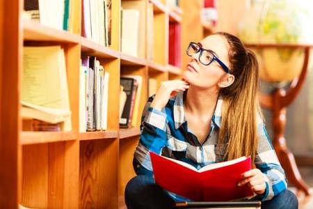 moudrost: Vzdělávání koncepce školy. Chytrá žena student vlasy cop dívka modré brýle sedí na podlaze v vysokoškolská knihovna s stoh knih. Krytý