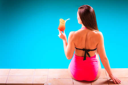 Spa relax and holidays concept. Sensual woman buttocks in swimsuit back view. Fit female body, girl sitting at poolside with cocktail glass photo