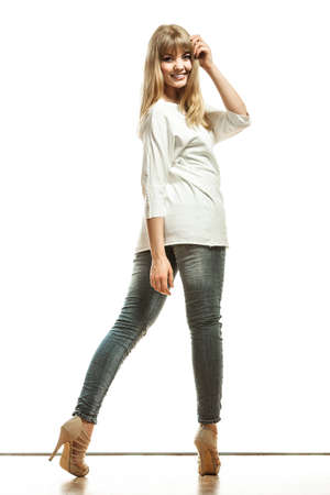 Fashion. Young blonde woman denim pants white bat sleeve top high heels. Female model posing in full length isolated Stock Photo