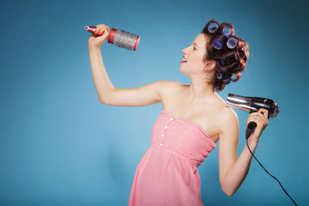 drier: Young woman preparing to party having fun, amusing girl styling hair with curlers hairbrush and hairdreyer retro style blue background Stock Photo