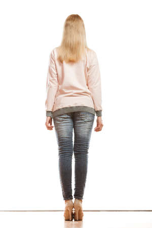 denim trousers: Fashion. Woman full length in denim trousers high heels shoes casual style back view isolated
