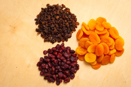 dehydrated: Healthy food organic nutrition. Dried dehydrated fruits raisins apricots and cranberries on wooden table Stock Photo