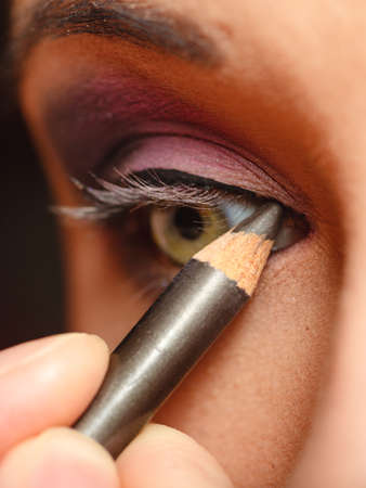 makeover: Cosmetic beauty procedures and makeover concept. Closeup part of woman face eye makeup detail. Using color pencil Stock Photo