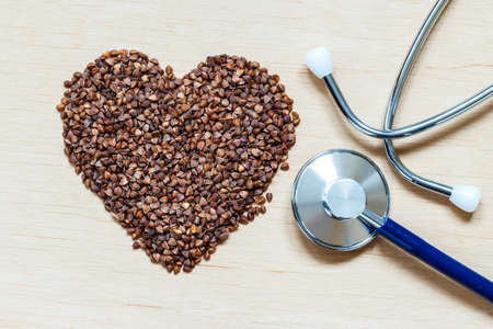 cardiovascular system: Dieting healthy living concept. Buckwheat groats heart shaped and stethoscope on wooden surface.. Healthy food good for cardiovascular system Stock Photo
