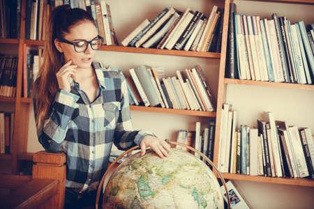 wereldbol: Onderwijs reizen en geografie concept. Jonge mooie vrouw vrouwelijke student in blauwe glazen in bibliotheek wijst naar globe Stockfoto