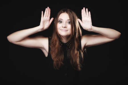 bruit: Gossip scandal or secrets. Young woman teen girl with hands to ear listening on black Stock Photo