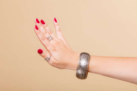 armlet: Closeup female hand, woman showing fashionable accessories bijouterie armlet and rings on finger. Beauty red nails.