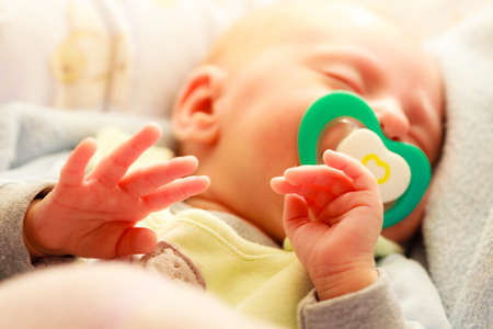 nipple girl: Closeup little newborn baby girl 24 days sleeping with dummy in mouth Stock Photo