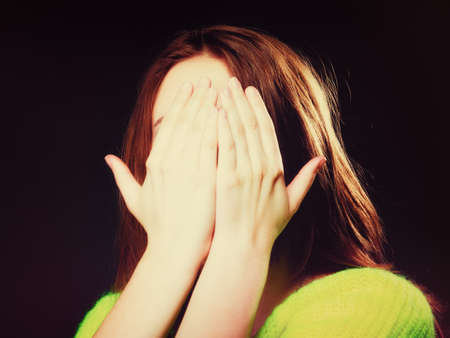 perturbed: Scared. young woman teen girl covering her face with hands palms on black. No see evil