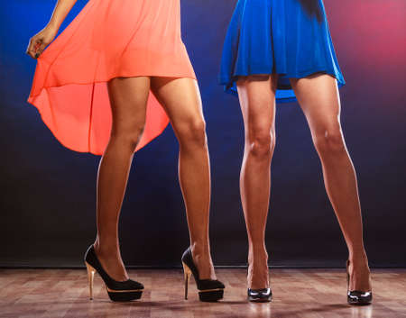 Legs and heels: Party, celebration, disco concept. Women in evening dresses dancing in the club, part of body female legs in high heels on party floor.